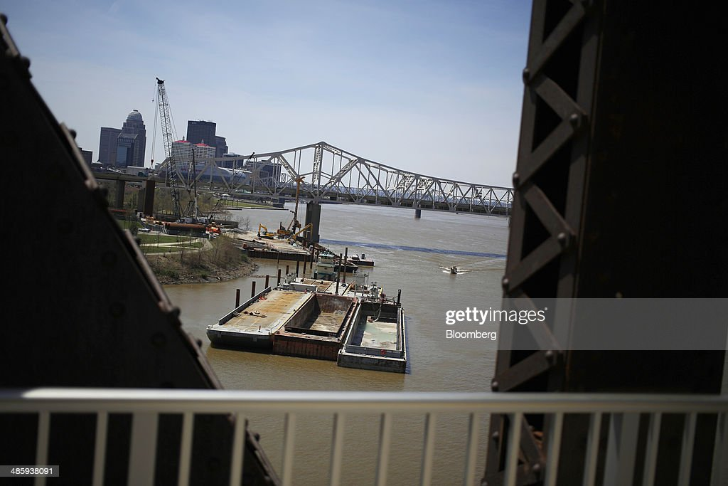 Construction barges sit underneath the Interstate 65 bridge on the Ohio River in Louisville Kentucky US on Thursday April 17 2014 Commercial traffic...