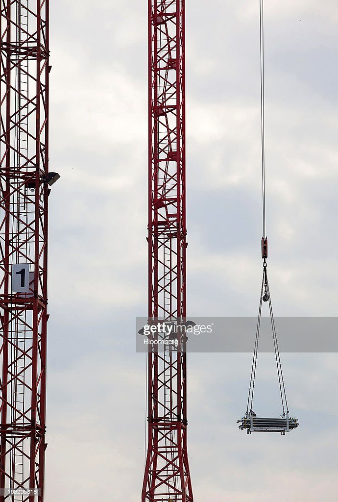 A construction crane is seen moving building material around a construction site in the city center of Berlin, Germany, on Tuesday, May 7, 2013. Germany, Europe's largest economy, reported growth in the construction industry during April, according to Markit Economics. Photographer: Krisztian Bocsi/Bloomberg via Getty Images