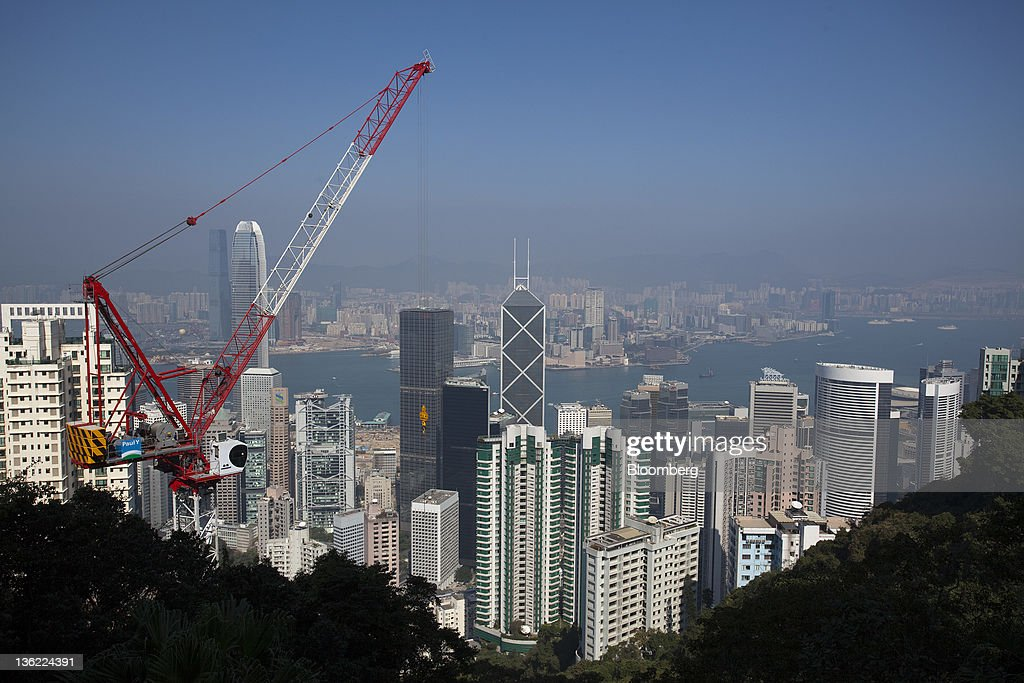 A construction crane operates as residential and commercial buildings rise above the business district of Central in Hong Kong, China, on Thursday, Dec. 29, 2011. Hong Kong stocks fell today after a surge in lending by the European Central Bank underscored the scale of the region's debt crisis. Photographer: Jerome Favre/Bloomberg via Getty Images