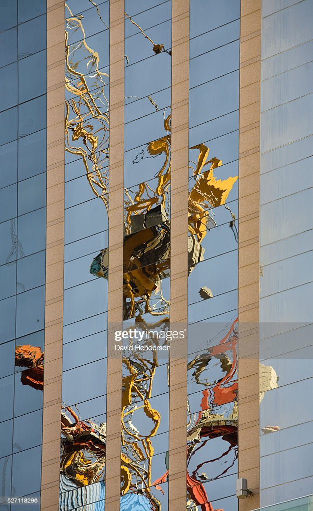 Construction crane reflected in the windows of a skyscraper : Stock Photo