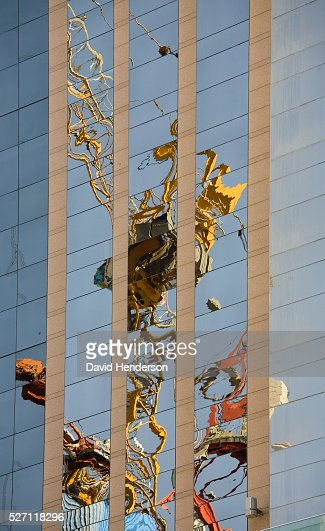 Construction crane reflected in the windows of a skyscraper : Bildbanksbilder