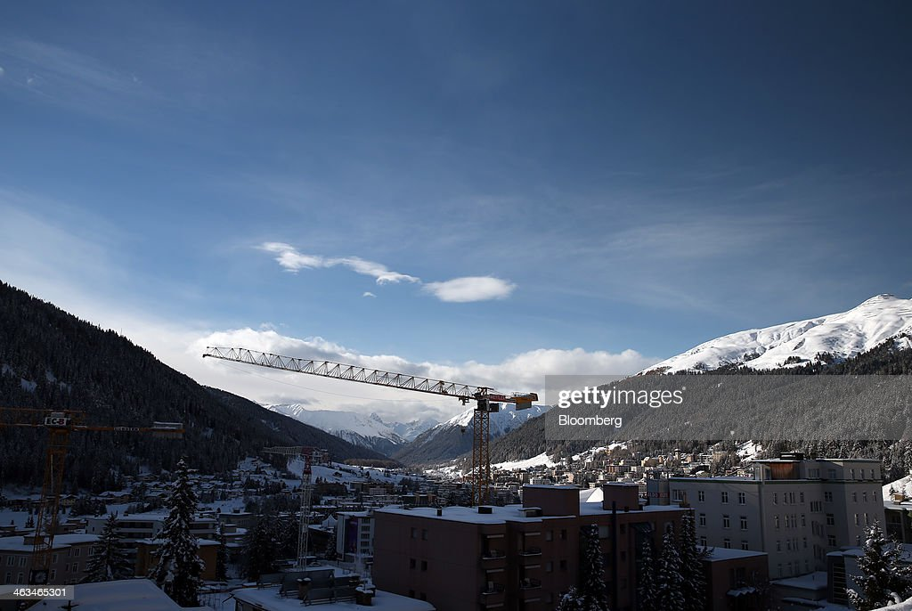 A construction crane rises above snow covered buildings in the town of Davos, Switzerland, on Saturday, Jan. 18, 2014. Next week the business elite will gather in the Swiss Alps for the 44th annual meeting of the World Economic Forum (WEF) in Davos for the five day event which runs from Jan. 22-25. Photographer: Simon Dawson/Bloomberg via Getty Images