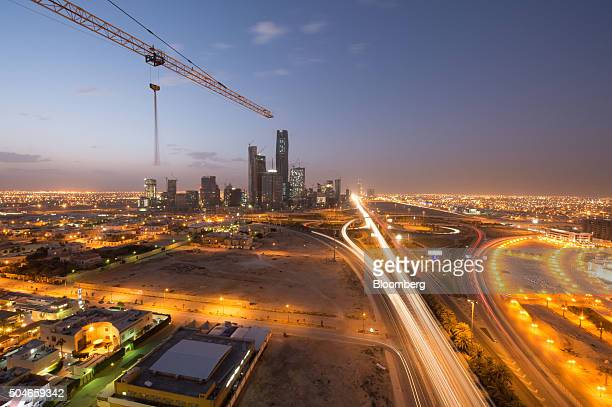 A construction crane sits above an illuminated highway leading past the King Abdullah financial district center in Riyadh Saudi Arabia on Friday Jan...