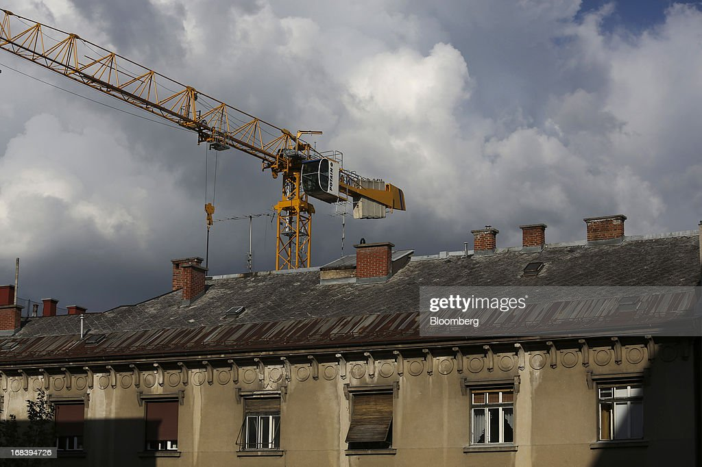 A construction crane stands above residential buildings in Ljubljana, Slovenia, on Wednesday, May 8, 2013. Slovenia's recession will stretch into next year on weak domestic demand as the euro-area country teeters on the brink of needing an international bailout, the European Commission said. Photographer: Chris Ratcliffe/Bloomberg via Getty Images