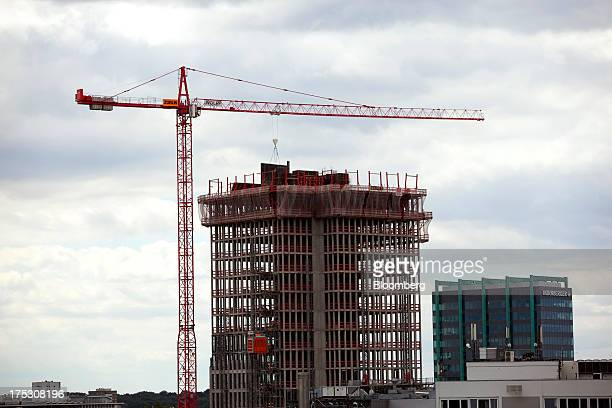 A construction crane stands next to a incomplete building as the offices of insurer Nurnberger Lebensversicherung AG right stand in Frankfurt Germany...