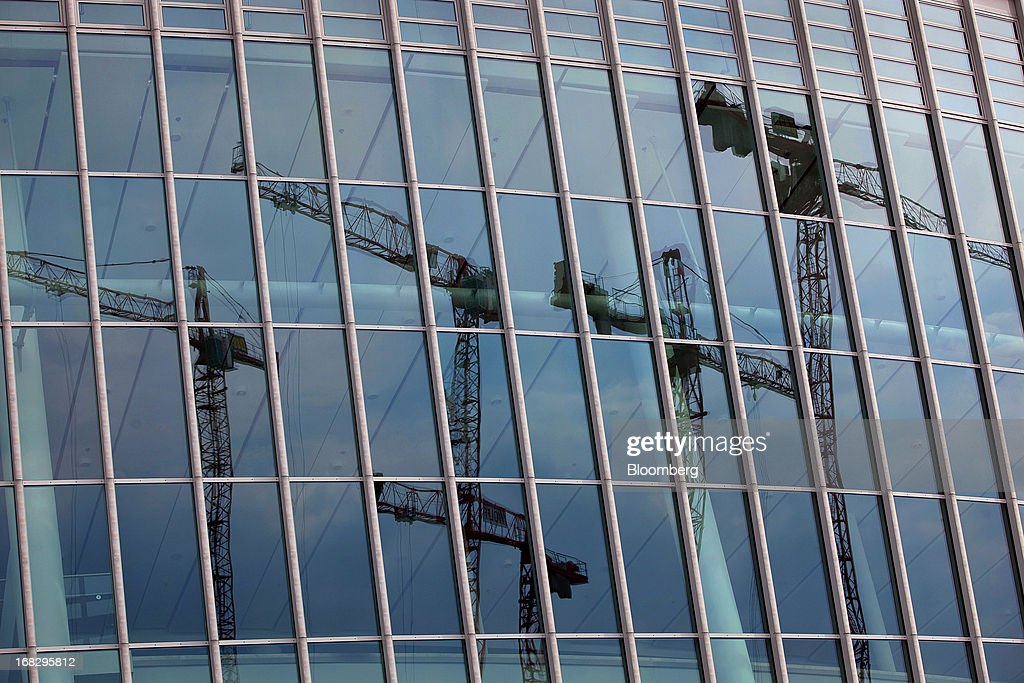 Construction cranes are seen reflected in the windows of a building located in the city center of Berlin, Germany, on Tuesday, May 7, 2013. Germany, Europe's largest economy, reported growth in the construction industry during April, according to Markit Economics. Photographer: Krisztian Bocsi/Bloomberg via Getty Images