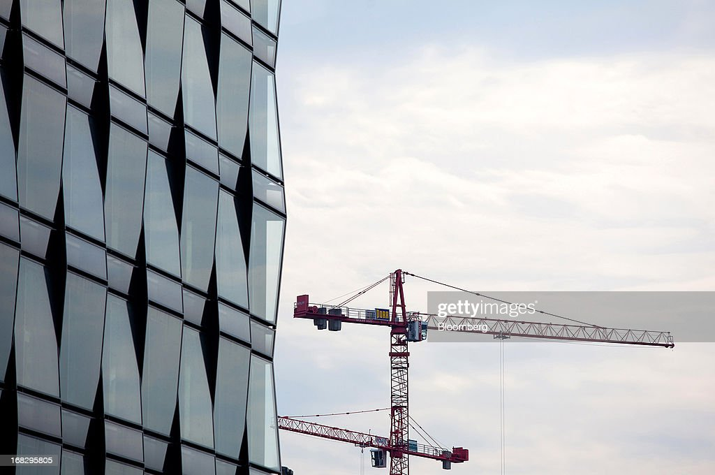 Construction cranes are seen rising from a building in the city centre of Berlin, Germany, on Tuesday, May 7, 2013. Germany, Europe's largest economy, reported growth in the construction industry during April, according to Markit Economics. Photographer: Krisztian Bocsi/Bloomberg via Getty Images