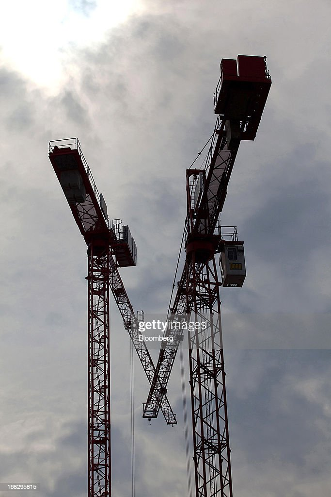 Construction cranes are seen rising from a building in the city center of Berlin, Germany, on Tuesday, May 7, 2013. Germany, Europe's largest economy, reported growth in the construction industry during April, according to Markit Economics. Photographer: Krisztian Bocsi/Bloomberg via Getty Images