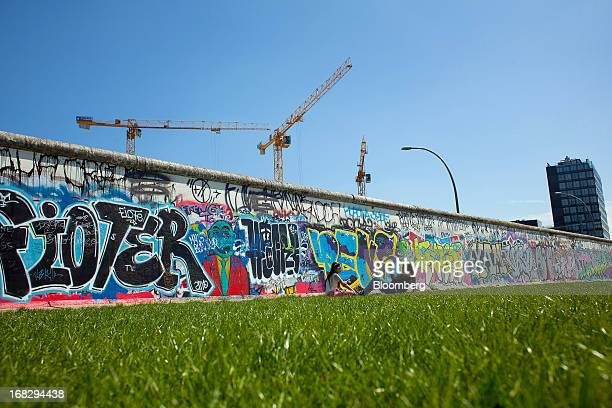 Construction cranes are seen rising from a building site above a section of the Berlin Wall's East Side gallery in Berlin Germany on Tuesday May 7...