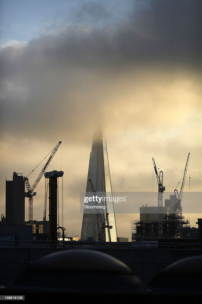 Construction cranes for new commercial buildings surround the Shard tower in London, U.K., on Friday, Dec. 21, 2012. Britain's economy expanded less than previously estimated in the third quarter and the budget deficit unexpectedly widened in November, complicating Prime Minister David Cameron's attempts to bolster the recovery. Photographer: Simon Dawson/Bloomberg via Getty Images