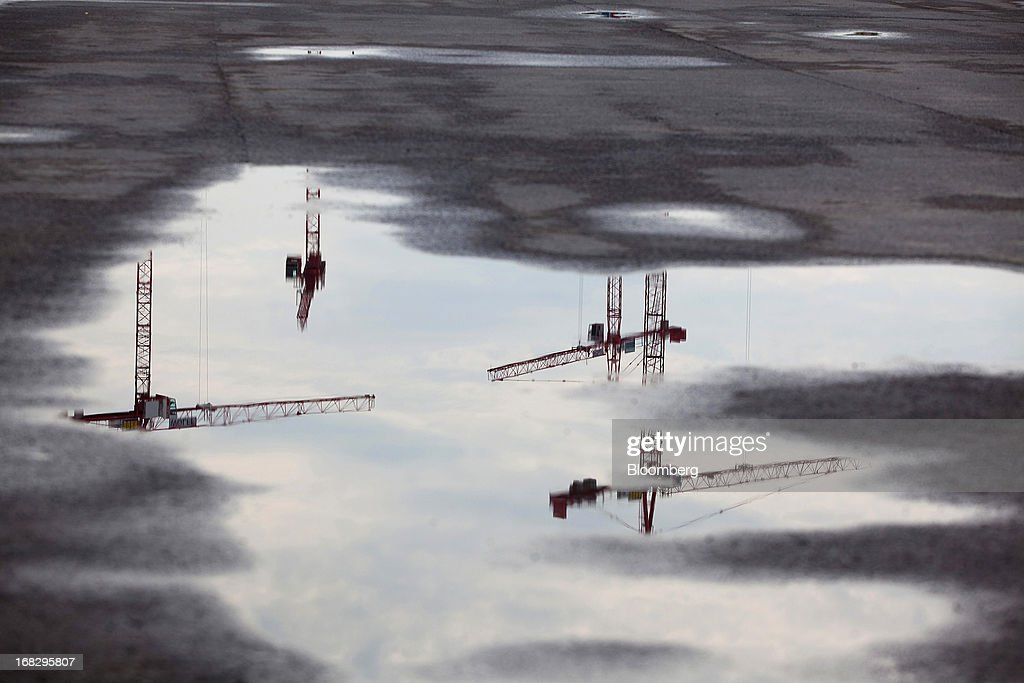 Construction cranes located on a building site are seen reflected in pools of rain water formed on a pavement in Berlin, Germany, on Tuesday, May 7, 2013. Germany, Europe's largest economy, reported growth in the construction industry during April, according to Markit Economics. Photographer: Krisztian Bocsi/Bloomberg via Getty Images