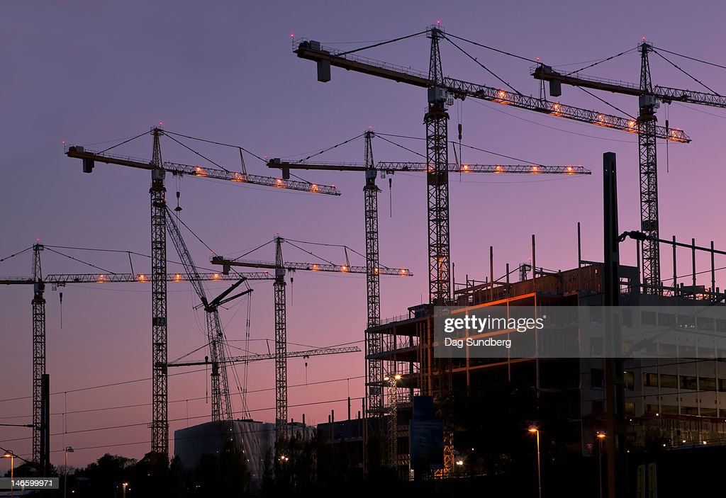 Construction cranes on a building site at night : Stock Photo