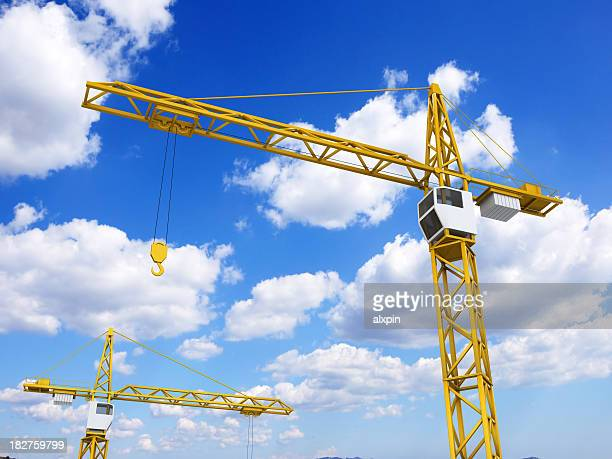 Construction cranes on sky background
