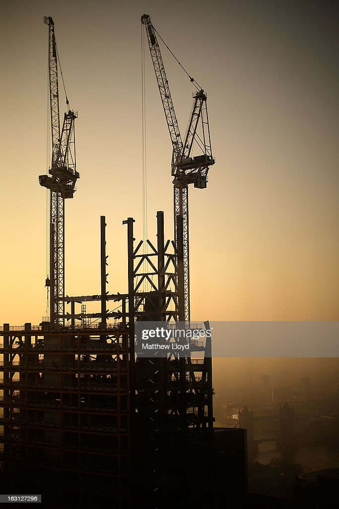 Construction cranes on top of the 122 Leadenhall St skyscraper, nicknamed the Cheesegrater, are silhouetted at sunrise on March 5, 2013 in London, England. The recent construction of numerous tall buildings on the London skyline has been controversial due to concerns that views of historic landmark buildings, such as St Paul's cathedral, are being obscured.