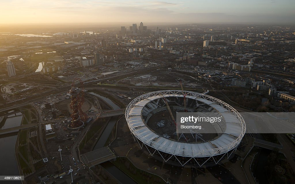 Construction cranes operate inside the London 2012 Olympic Stadium right in this aerial photograph looking towards the Canary Wharf business and...