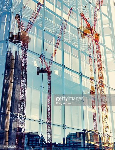 Construction cranes reflected in office windows