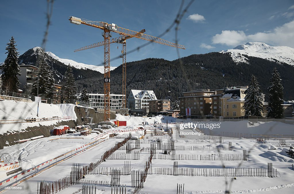 Construction cranes rise above a building site and snow covered houses in the town of Davos, Switzerland, on Saturday, Jan. 18, 2014. Next week the business elite will gather in the Swiss Alps for the 44th annual meeting of the World Economic Forum (WEF) in Davos for the five day event which runs from Jan. 22-25. Photographer: Simon Dawson/Bloomberg via Getty Images
