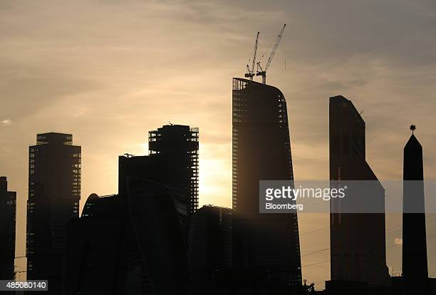 Construction cranes sit above a skyscraper in the Moscow City business district in Moscow Russia on Sunday Aug 23 2015 The Russian ruble plunged 23...