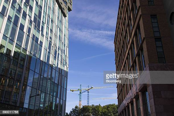 Construction cranes sit beyond commercial office properties in the Zuidas business district of Amsterdam Netherlands on Monday Aug 15 2016 The Dutch...