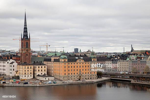 Construction cranes sit on the city skyline beyond historic buildings in the Old Town district of Stockholm Sweden on Monday Oct 19 2015 As Sweden's...