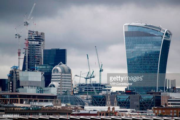 Construction cranes stand around skyscrapers in the City of London including 20 Fenchurch Street commonly called the 'WalkieTalkie' building as they...