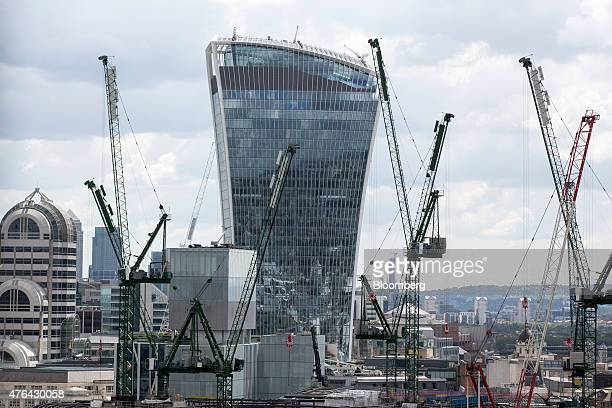 Construction cranes stand beside 20 Fenchurch Street also known as the 'WalkieTalkie' in the City of London financial district in London UK on Monday...