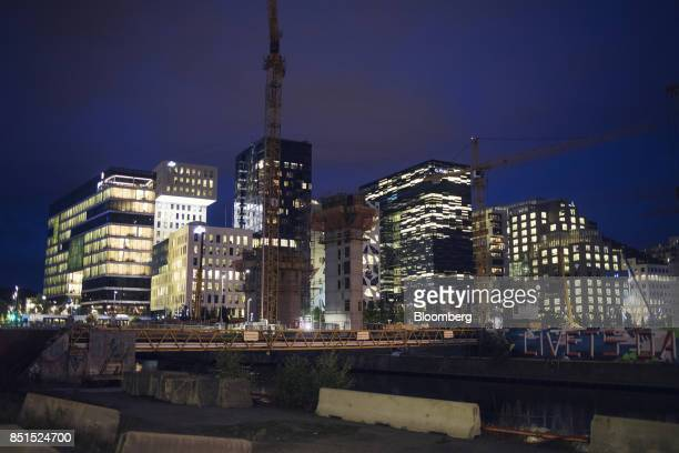 Construction cranes stand beside a dock under redevelopment near illuminated buildings in the Barcode development area in Oslo Norway on Wednesday...