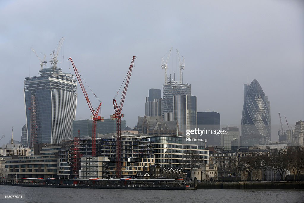 Construction cranes stand beside the River Thames near the Three Quays building, center left, and 20 Fenchurch Street, or the 'Walkie-Talkie' building, left, alongside the Leadenhall Building, also known as the 'Cheesegrater', center, and the The Swiss Re Insurance building, also known as 'the Gherkin' right, in London, U.K., on Monday, March 4, 2013. Central London luxury-home prices unexpectedly rose at the fastest pace in 10 months in February as the British pound's depreciation helped attract international investors, Knight Frank LLP said. Photographer: Simon Dawson/Bloomberg via Getty Images