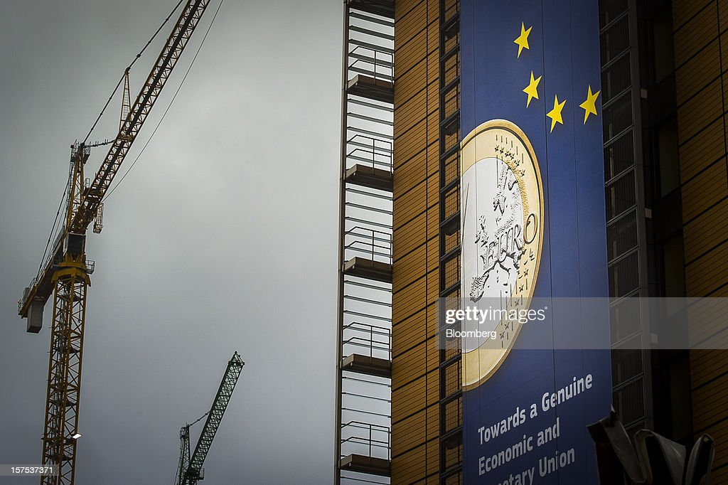 Construction cranes stand near a giant banner promoting the euro currency and economic union on the exterior of the European Commission headquarterss in Brussels, Belgium, on Tuesday, Dec. 4, 2012. European finance ministers voiced confidence that Greece will pull off a successful bond buyback, the key element in a revamped effort to stem the debt crisis in the country where it started. Photographer: Jock Fistick/Bloomberg via Getty Images
