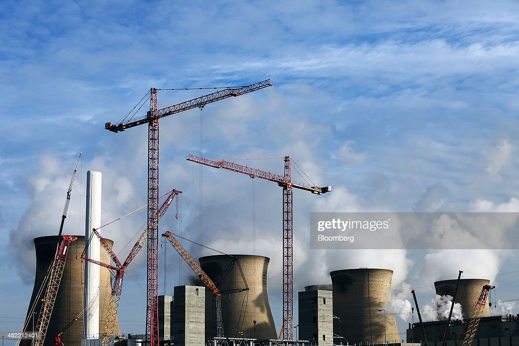 Construction cranes stand on the site of a new multi-fuel plant as cooling towers emit vapor at Ferrybridge coal fired power station, operated by SSE Plc, in Ferrybridge, U.K., on Tuesday Nov. 26, 2013. SSE Plc, the U.K.'s second-biggest energy supplier, pledged to curb increases in customer bills if the government cuts environmental levies that push up tariffs. Photographer: Chris Ratcliffe/Bloomberg via Getty Images