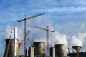 Construction cranes stand on the site of a new multifuel plant as cooling towers emit vapor at Ferrybridge coal fired power station operated by SSE...