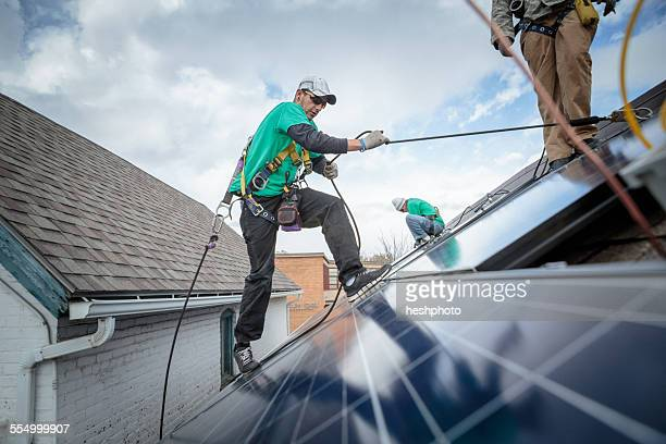 Construction crew installing solar panels on a house