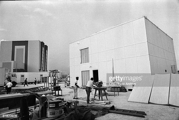 Construction crew members work near the CBS News building and the Vehicle Assembly Building during production of segments for the CBS News report...