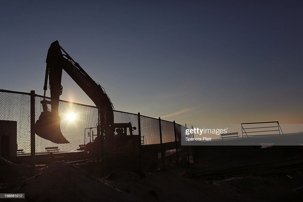 A construction crew works on part of the boardwalk at dawn in the heavily damaged Rockaway neighborhood, where a large section of the iconic boardwalk was washed away on November 19, 2012 in the Queens borough of New York City. As the holidays approach after Superstorm Sandy slammed into parts of New York and New Jersey, thousands of residents and businesses are still recovering from the devastation.