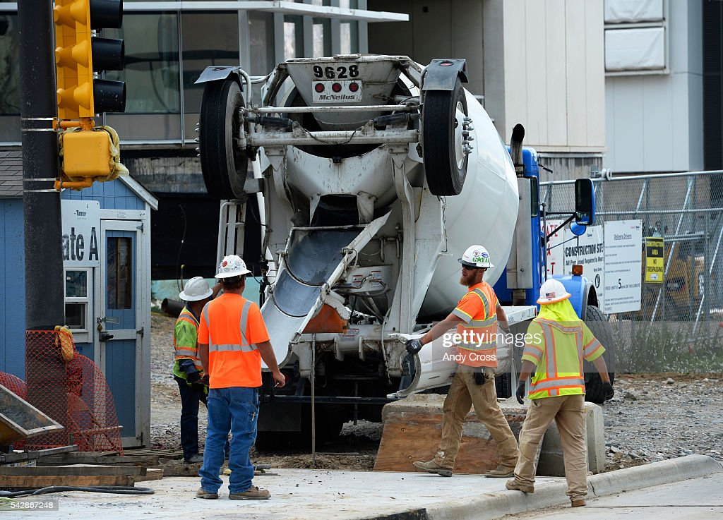 Construction crews work on a sidewalk in front of the new VA Hospital June 24, 2016.