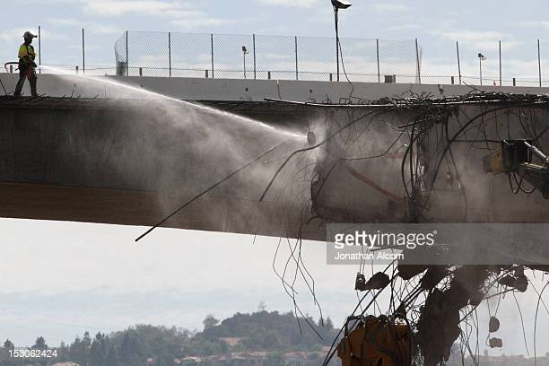 Construction crews work to demolish a portion of the Mulholland Drive bridge along the 405 Freeway September 29 2012 in Los Angeles California The...