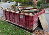 Filled red industrial construction dumpster curbside in residential neighborhood. Horizontal.