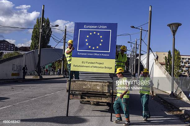 Construction employees unload a placard bearing the EU logo as they work on the reconstruction of the main bridge in the divided town of Mitrovica on...