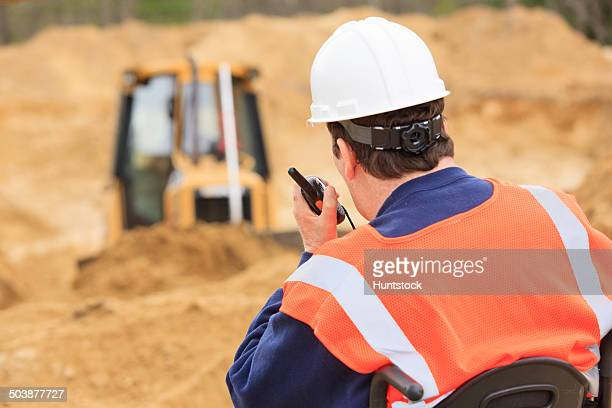 Construction engineer with spinal cord injury on radio to equipment operator
