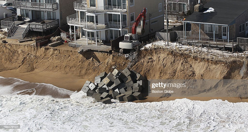 Construction equipment lowers blocks onto the beach to protect homes on the coast of Plum Island. Several houses were structurally damaged during yesterday's winter storm and two fell off their foundations.