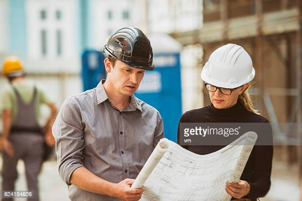 Construction foreman and architect reviewing blueprints