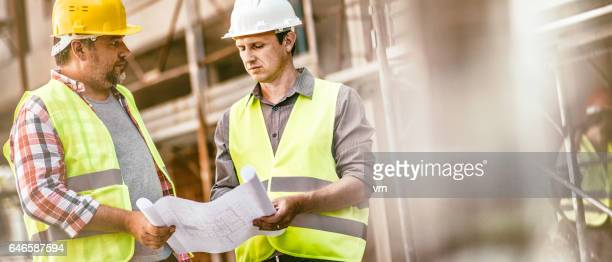 Construction foreman consulting an architect on construction site