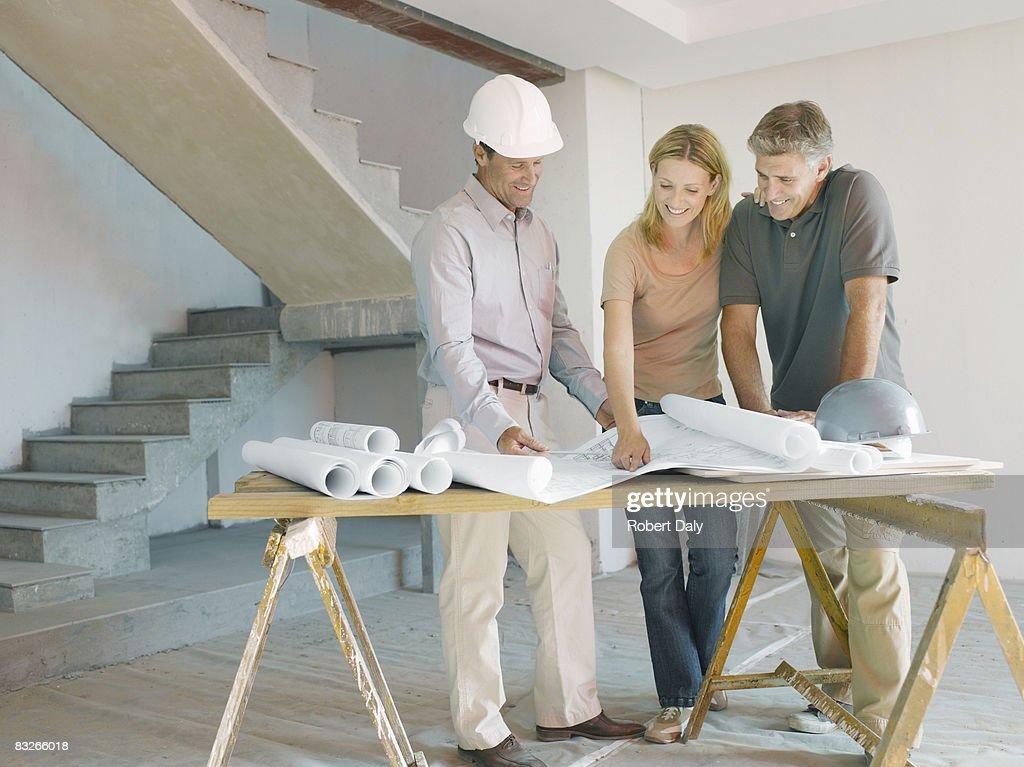 Construction foreman explaining blueprints to couple : Stock Photo