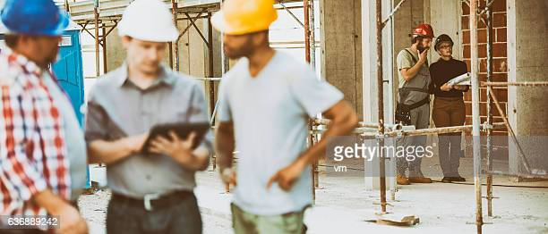 Construction foreman explaining construction plan to workers