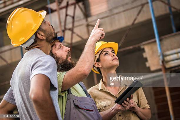 Construction foreman explaining current progress to architects