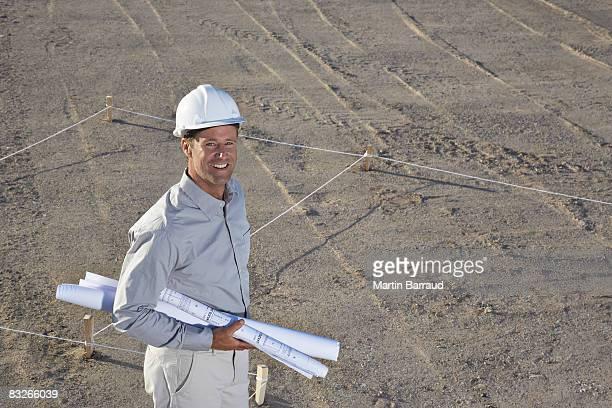 Construction foreman holding blueprints on construction site