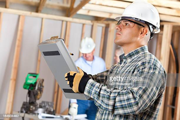 Construction foreman inspecting work at a house building site