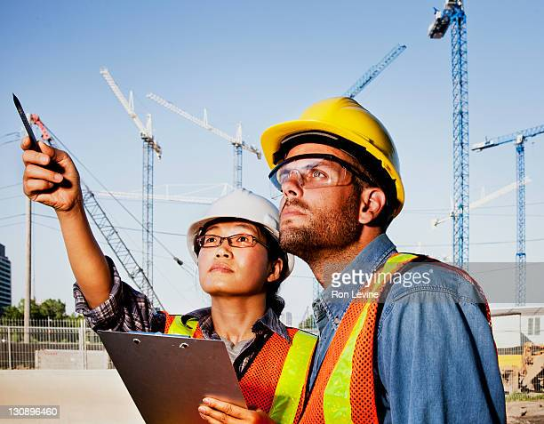 Construction forman pointing out detail to worker