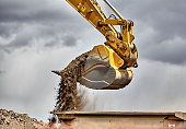 Construction industry heavy equipment excavator moving gravel at jobsite quarry with stormy skies