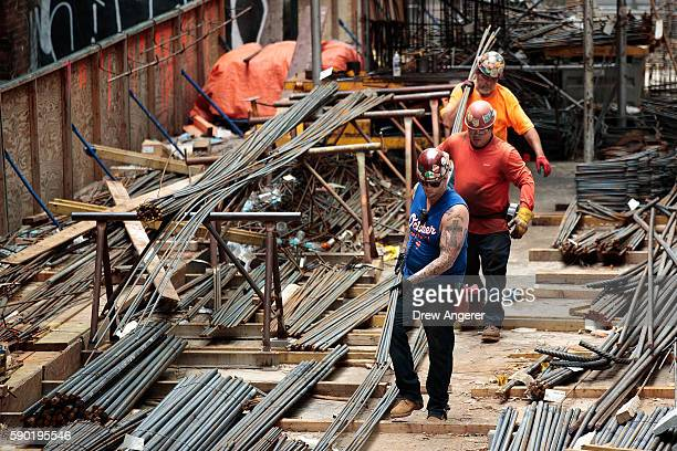 Construction laborers work on the site of a new residential building in the Hudson Yards development August 16 2016 in New York City Home...